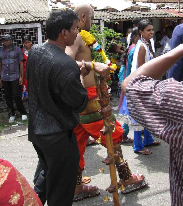 photo of man walking in nail shoes (burden of Thaipusam)
