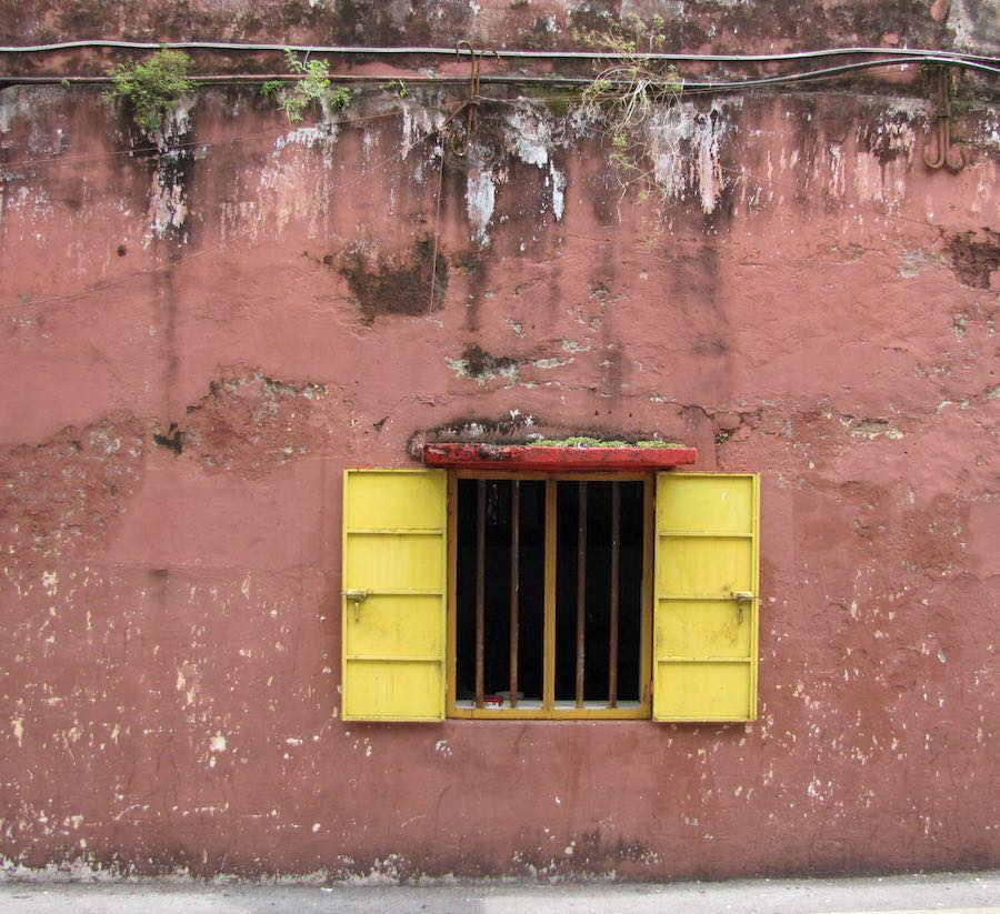 Window on a red wall with yellow shutters open